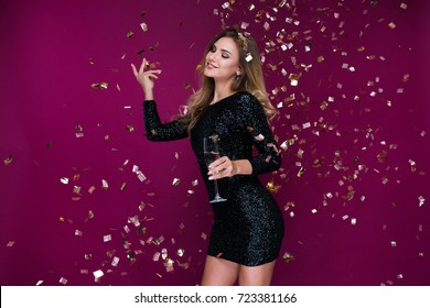 Happy New Year to you! One beautiful young woman with confetti, celebration Christmas with glass of champagne. New Year's party. Christmas Eve.