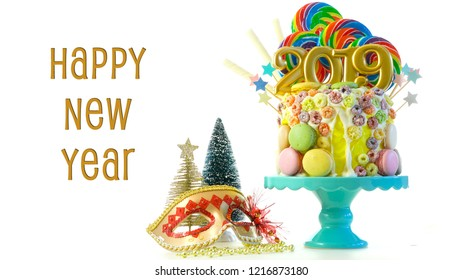 Happy New Year's candy land lollipop drip cake with 2019 candles on white background with text greeting.