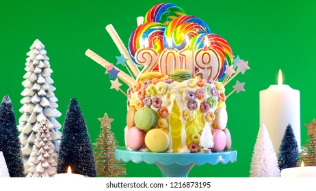 Happy New Year's candy land lollipop drip cake with 2019 candles on green chroma key background.