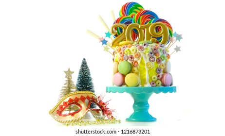 Happy New Year's candy land lollipop drip cake with 2019 candles on white background.