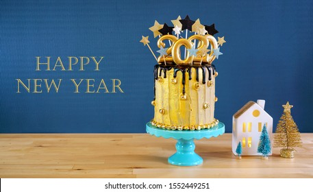 Happy New Year's Eve 2020 black and gold drip cake on a modern stylish, festive, blue gold and white winter theme table setting with text greeting message.
