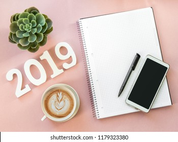 Happy New Year's layout. numbers 2019 notepad and free space for text. Christmas decorations, Christmas toys, gold stars. Goals for the new year. mock up mobile phone. To do list. Flatlay