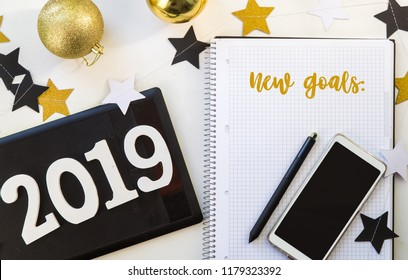 Happy New Year's layout. numbers 2019 notepad and free space for text. Christmas decorations, Christmas toys, gold stars. Goals for the new year. mock up mobile phone. flatlay , xmas. To do list