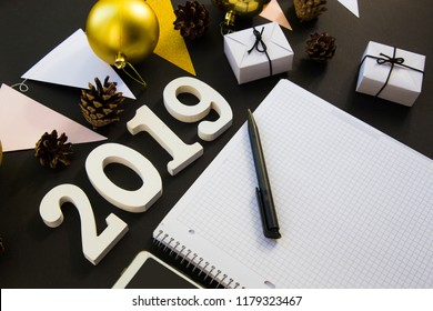 Happy New Year's layout. numbers 2019 notepad and free space for text. Christmas decorations, Christmas toys, gifts, gold stars. Goals for the new year. mock up mobile phone on black background