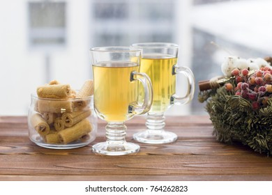 Happy New Year's morning with glass tea cups, a bowl of cookies and a pine wreath,light background