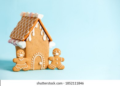 Happy New Year's set of house, gingerbread man in face mask from ginger biscuits glazed sugar icing decoration on blue background, minimal seasonal pandemic winter holiday banner, stay home - Shutterstock ID 1852111846