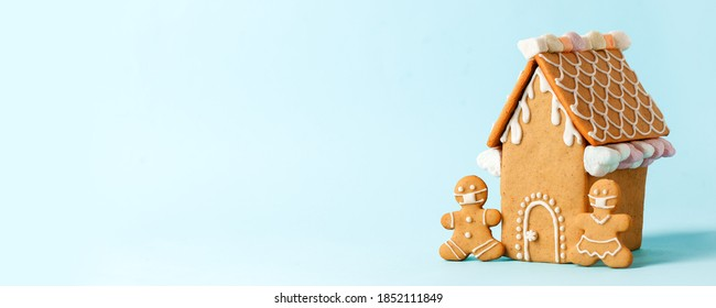 Happy New Year's set of house, gingerbread man in face mask from ginger biscuits glazed sugar icing decoration on blue background, minimal seasonal pandemic winter holiday banner, stay home - Shutterstock ID 1852111849