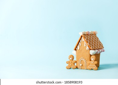 Happy New Year's set of house, gingerbread man in face mask from ginger biscuits glazed sugar icing decoration on blue background, minimal seasonal pandemic winter holiday banner, stay home - Shutterstock ID 1858908193