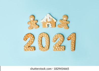 Happy New Year's set of numbers 2021, gingerbread man in face mask from ginger biscuits glazed sugar icing decoration on blue background, minimal seasonal pandemic winter holiday card