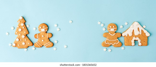Happy New Year's set of numbers 2021, gingerbread man in face mask from ginger biscuits glazed sugar icing decoration on blue background, minimal seasonal pandemic winter holiday banner - Shutterstock ID 1831365652