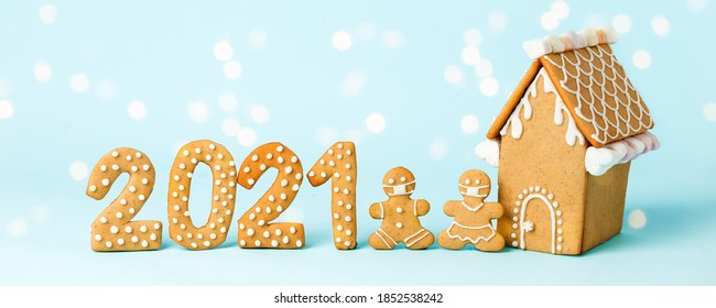 Happy New Year's set of numbers 2021, gingerbread man in face mask, house from ginger biscuits glazed sugar icing decoration on blue background, minimal seasonal pandemic winter holiday card - Shutterstock ID 1852538242