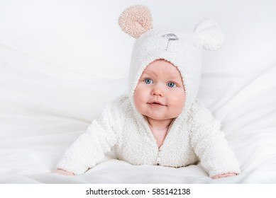 Happy newborn baby in a knitted bears costume on white isolated background.
