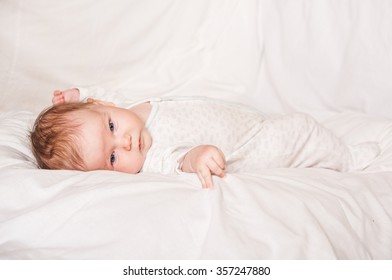 Happy newborn baby lying on white sheet and holding his legs