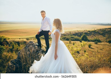 happy newly married couple posing in the mountains