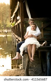 Happy newly married couple relaxing on old pier at forest