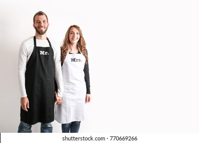Happy newly wed couple with kitchen utensils wearing Mr. and Mrs. Aprons