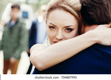 Happy newlywed bride hugging groom after wedding ceremony outdoors face close-up, newlywed couple portrait