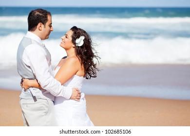 happy newlywed couple hugging on beach