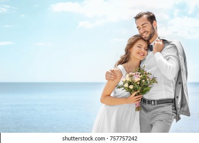 Happy newlywed couple hugging on seashore