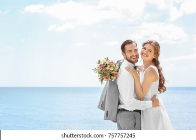Happy newlywed couple hugging on seashore