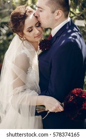 Happy newlywed couple hugging outdoors, portrait of groom kissing bride in white wedding dress in a summer park, happy moment concept
