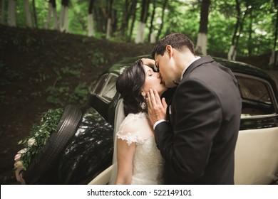 Happy newlywed couple, man and wife kissing near stylish retro car