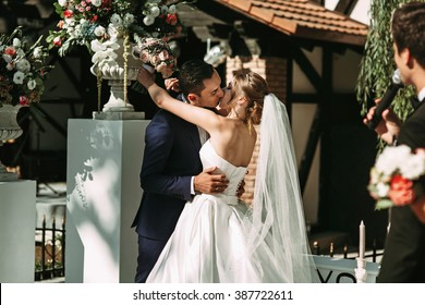 Happy newlywed couple posing & kissing at wedding aisle