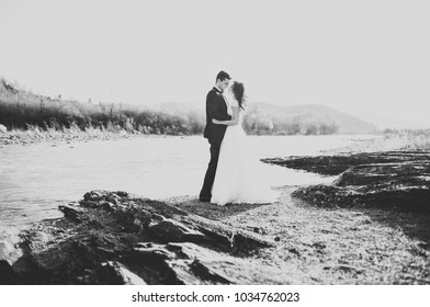 Happy newlywed couple posing and smiling in wedding dress and suit outdoor, black and white