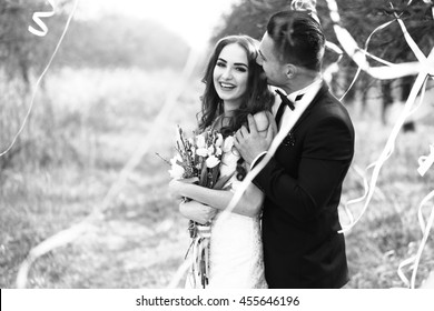 Happy newlywed couple posing and smiling in wedding dress and suit with flowers in forest decorated with ribbons outdoor, black and white