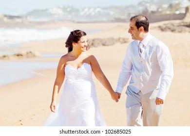 happy newlywed couple walking on beach