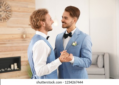 Happy newlywed gay couple dancing at home