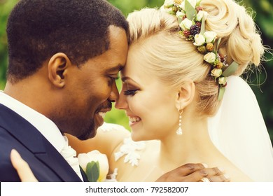 Happy newlyweds of beautiful bride blond woman with elegant hairstyle and african American groom man hug outdoors on wedding day