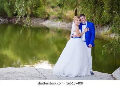 Happy newlyweds with beautiful lake behind
