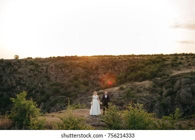 Happy newlyweds dance on the rocks