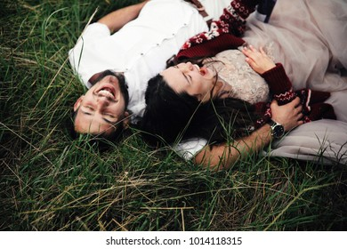 Happy newlyweds have fun lying on the lawn outside