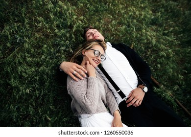 Happy newlyweds have fun lying on the green grass