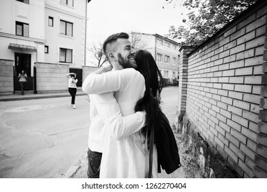 Happy newlyweds hug each other tender standing on the street