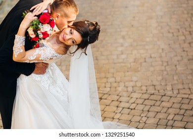 happy newlyweds kissing on the background of the pavement. the bride has bent back and holds a wedding bouquet