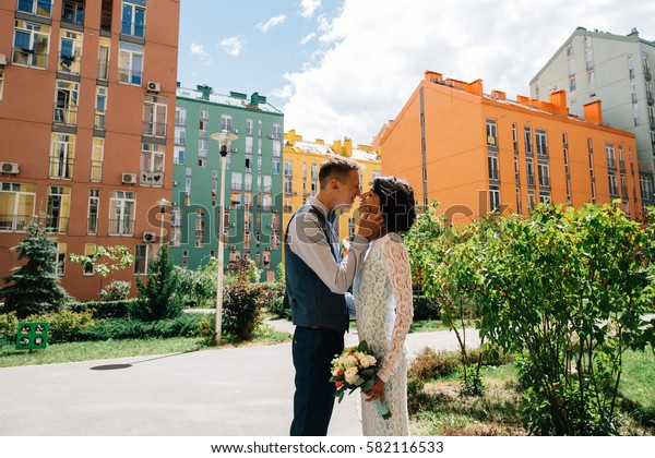 Happy newlyweds kissing on background of colorful buildings on wedding day