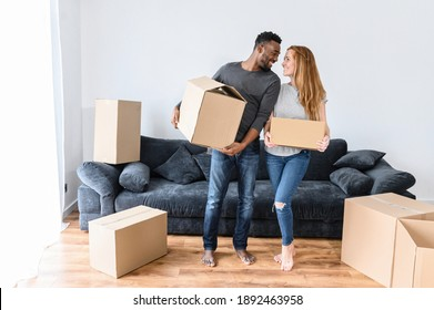 Happy newlyweds relocate to new apartment. Young married couple standing in living room, holding in arms cardboard boxes. Caucasian woman with african american man unpacking stuff, moving day concept