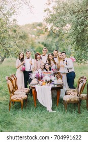 Happy newlyweds are sitting at the wedding table while their smiling bridesmaids and the best men are standing behind them at the background of the lovely green wood.