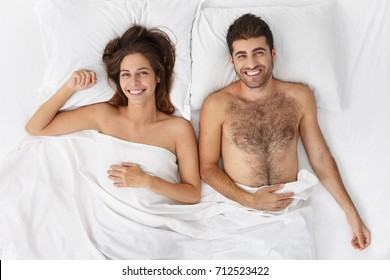Happy newlyweds spend wonderful wedding night together, have awesome mood as awakening in morning. Family have excellent relationship spend all day at bed. Unforgettable nighttime, pleasant emtions