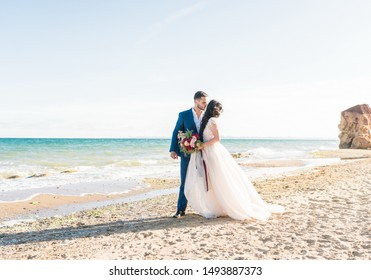Happy newlyweds stand holding hands on the background of the blue sea. Wedding walk on a sand beach. In the background, blue sky
