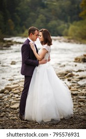 Happy newlyweds standing and smiling on the river bank