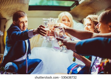 Happy newlyweds and their friends clang glasses in the limousine
