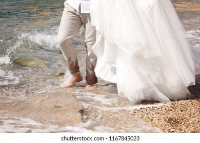 Happy newlyweds walking in sea waves on beach on their wedding day