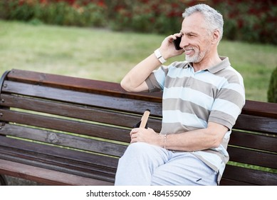 Happy nice-looking senior citizen smiling while talking on the phone