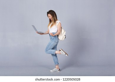 Happy nice-looking successfull student girl rejoices at excellent passing of exam, reads a letter from college by e-mail on laptop. American girl using digital computer for education or communication