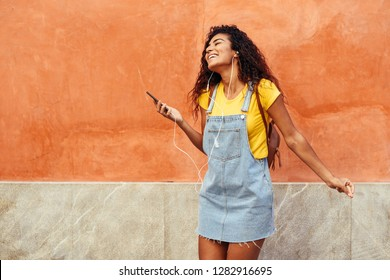 Happy North African woman listening to music and dancing with earphones outdoors. Arab girl in casual clothes with curly hairstyle in urban background.