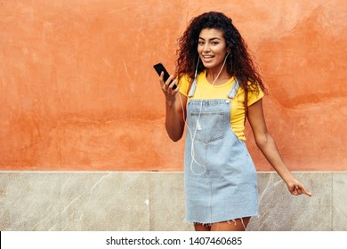 Happy North African woman listening to music with earphones outdoors. Arab girl in casual clothes with curly hairstyle on urban wall.